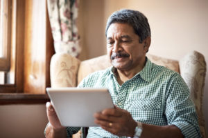Shot of a senior man using his digital tablet while relaxing at home