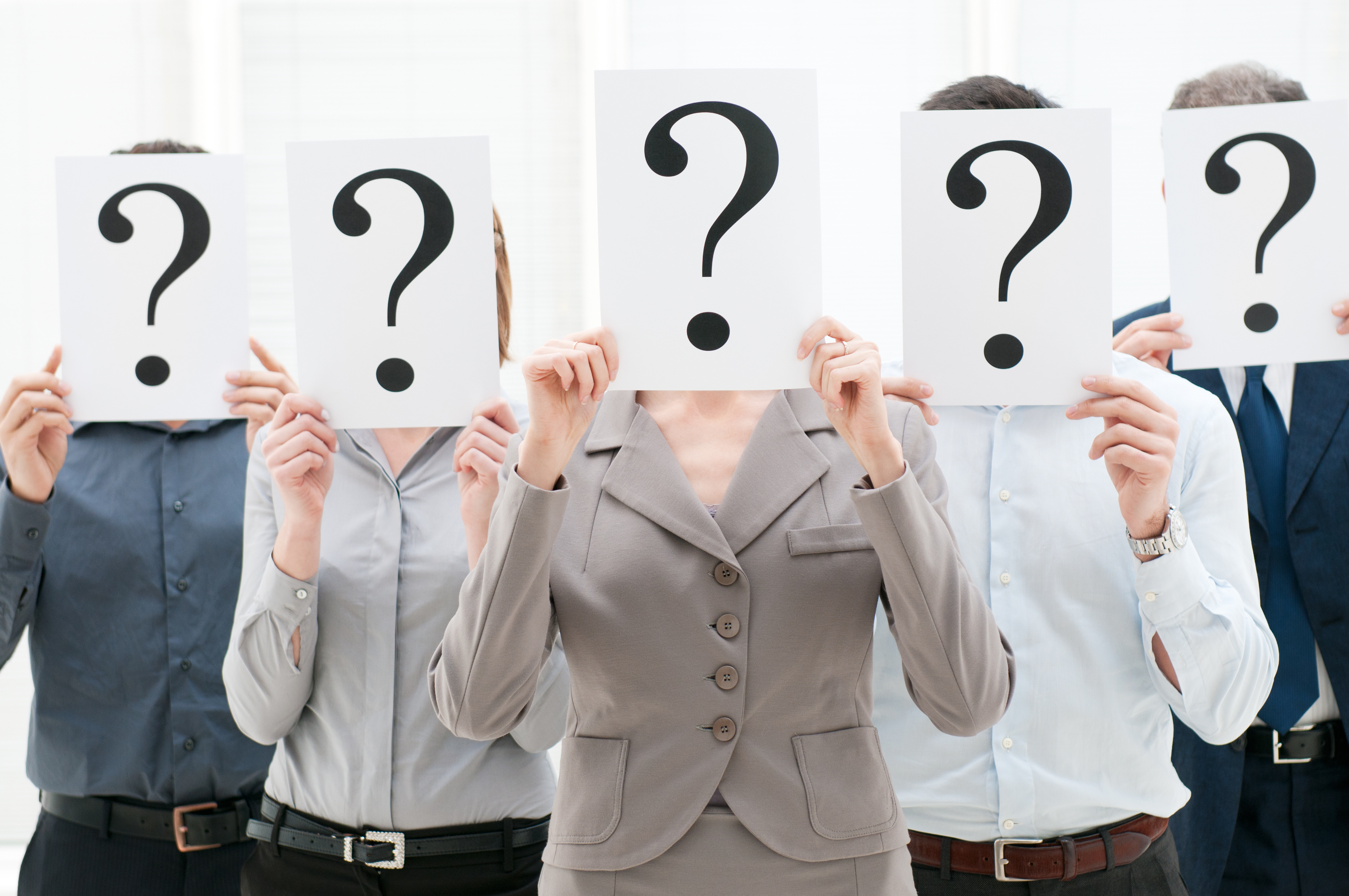 Business team hiding their faces behind question mark signs at office.