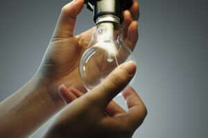 Hands of a person changing a light bulb isolated on dark blue background.