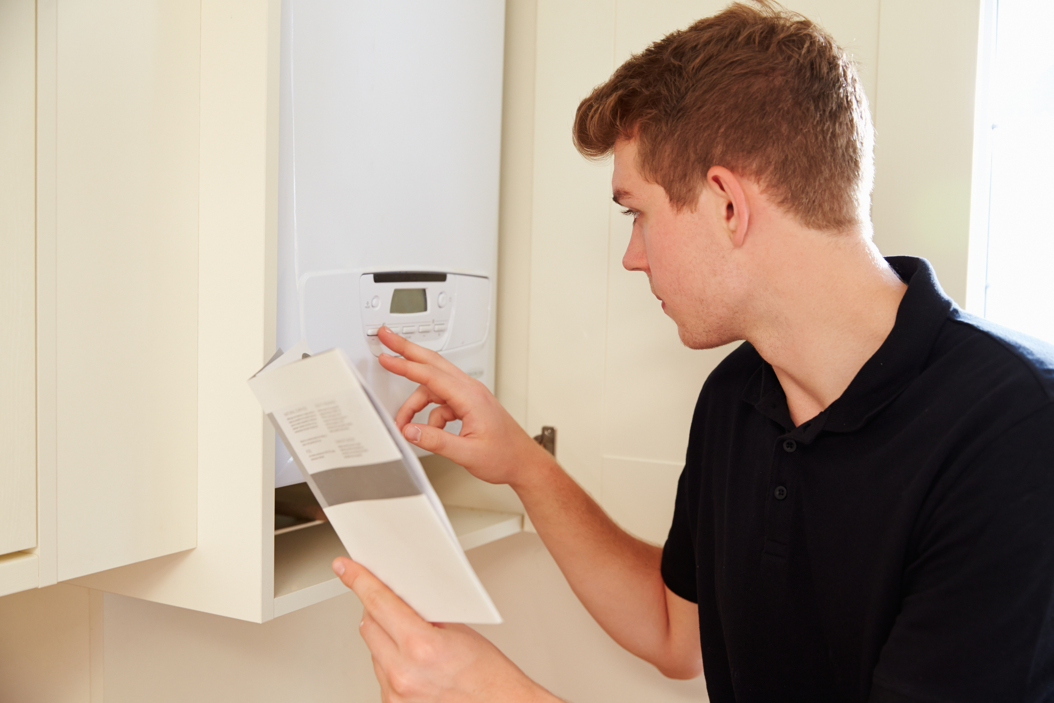 Young technician servicing a boiler, consulting manual